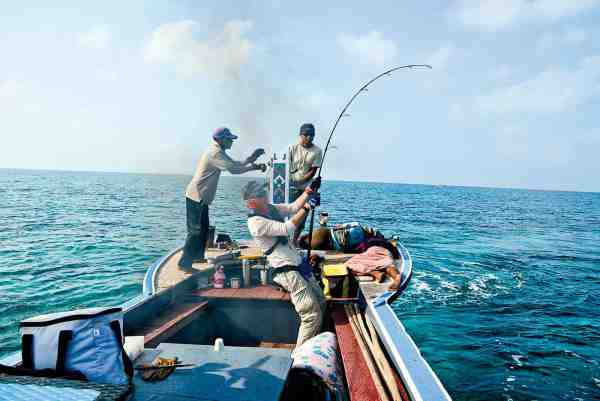 Fordelen ved ikke at stå på kasteplatformen bagerst i billedet og forrest på båden, er helt klart at man ikke så let bliver hevet over bord af de hvinende stærke fisk... Her er det Lars der må holde godt fat i stangen.