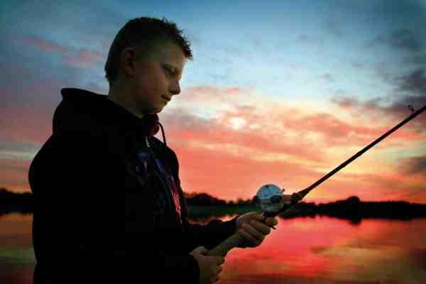 Unge Niklas nyder solnedgangen under en kort aftentur på Tuel Sø.