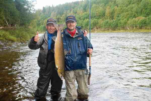 To glade venner, som har fisket sammen de sidste 25 år, er endelig igen sammen ved lakseelven. Til højre forfatteren og til venstre den professionelle fiskeguide Kenny Frost. Der er god grund til et 5,2 kilos laksesmil.