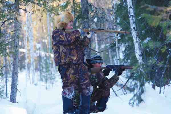 Et par lokale unge fyre på elgjagt for at supplere de sparsomme vinterforsyninger.
