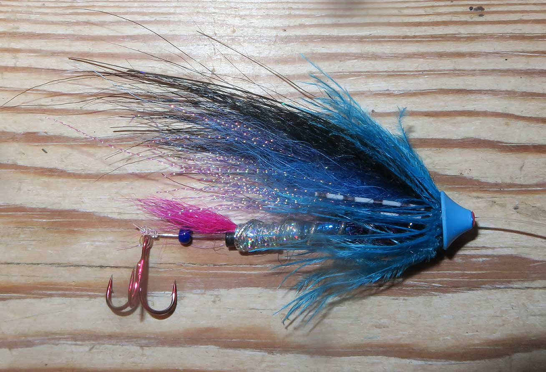 """Stefans egen flue – """"Kind of blue"""" er opkaldt efter et Miles Davis album plus selvfølgelig farven på fluen. Fluen er bundet på et tyndt rør, som er trukket på en 0,33 mm forfang og efterfulgt af en lille glasperle. Det tynde rør gør at perlen ikke glider ind i røret, og perlen sikrer at knuden hænger frit og dermed at krogen sidder løst efter røret."""