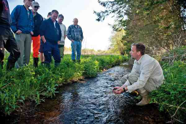 Finn Sivebæk holder hvert år kurser i vandløbsrestaurering og her fortæller han kursisterne om udlægning af gydegrus.