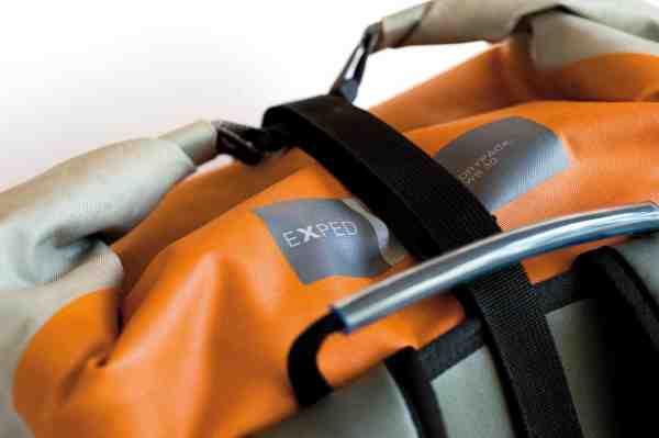 En topstrap som denne hjælper til at holde rullelukningen stram – og har den ekstra fordel, at den kan bruges til at påspænde ekstra gear i toppen. Et top håndtag på drybaggen er perfekt, når man skal flytte rundt på sækken på land – og godt når rygsækken skal hænges på knage i tørrerummet.