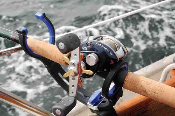 Det kan betale sig at tænke lidt over hvilket grej man vælger til fiskeriet fra sejlbåd. Her er der fx en aftagelig plastik stangholder fra Kinetic, der ikke ridser træværket, en tredelt rejsestang der let kan stuves væk i kahytten, og et Revo Toro hjul fra Abu Garcia, som har den fordel, at knarren larmer når der er hug.