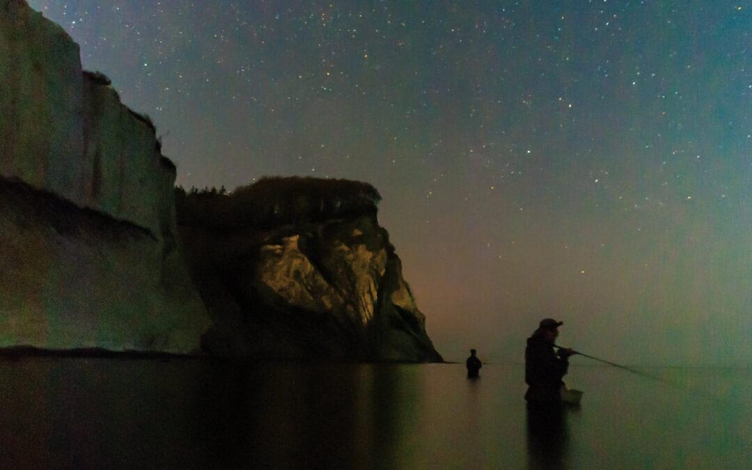 Man mærker naturens storhed og universets uendelighed når man står for foden af den monstrøse klint under stjernevrimmelen. Lasse og Jeppe spejder opmærksomt efter fisk i den blanke overflade.