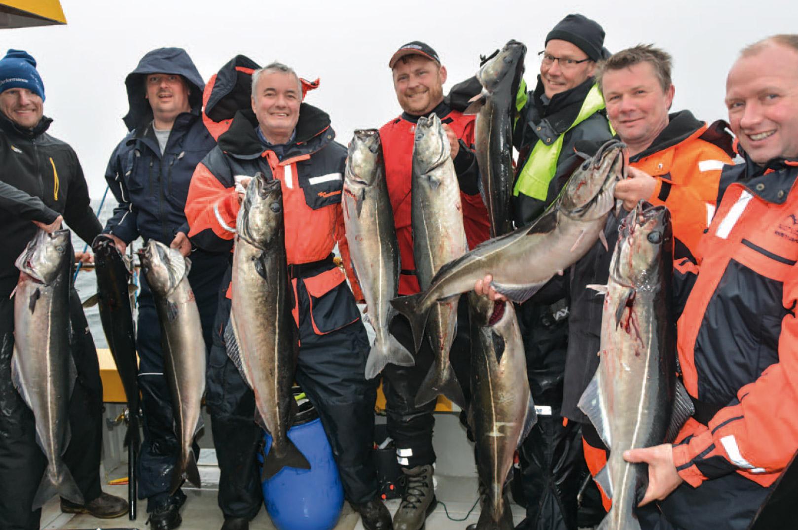 En flok glade havfiskere med en stribe flotte sej taget fra Seahawk.