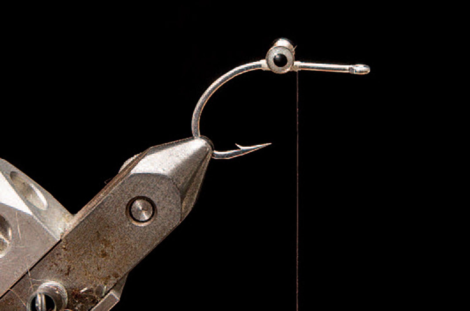 1: Bind dine dumbbell øjne ind på oversiden af krogen og giv efterfølgende en klat lim eller lak. De skal bindes godt fast så de ikke roterer under brug. Her er øjnene bundet ind nærmest lige over krogspidsen, men ved at rykke dem frem eller tilbage får man en mere eller mindre jiggende gang.