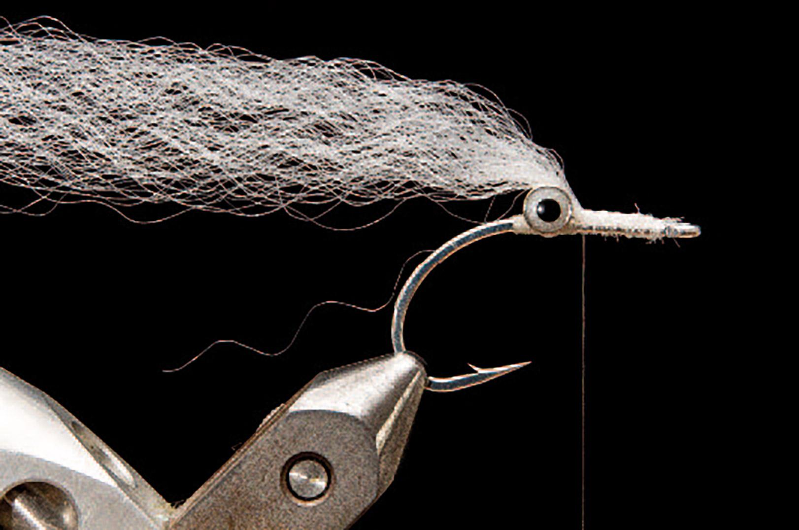 2: Bind dit lyse bundt syntetmateriale ind foran øjnene. I dette tilfælde er der brugt Unique Hair, men de fleste andre syntetiske vingematerialer virker også godt.