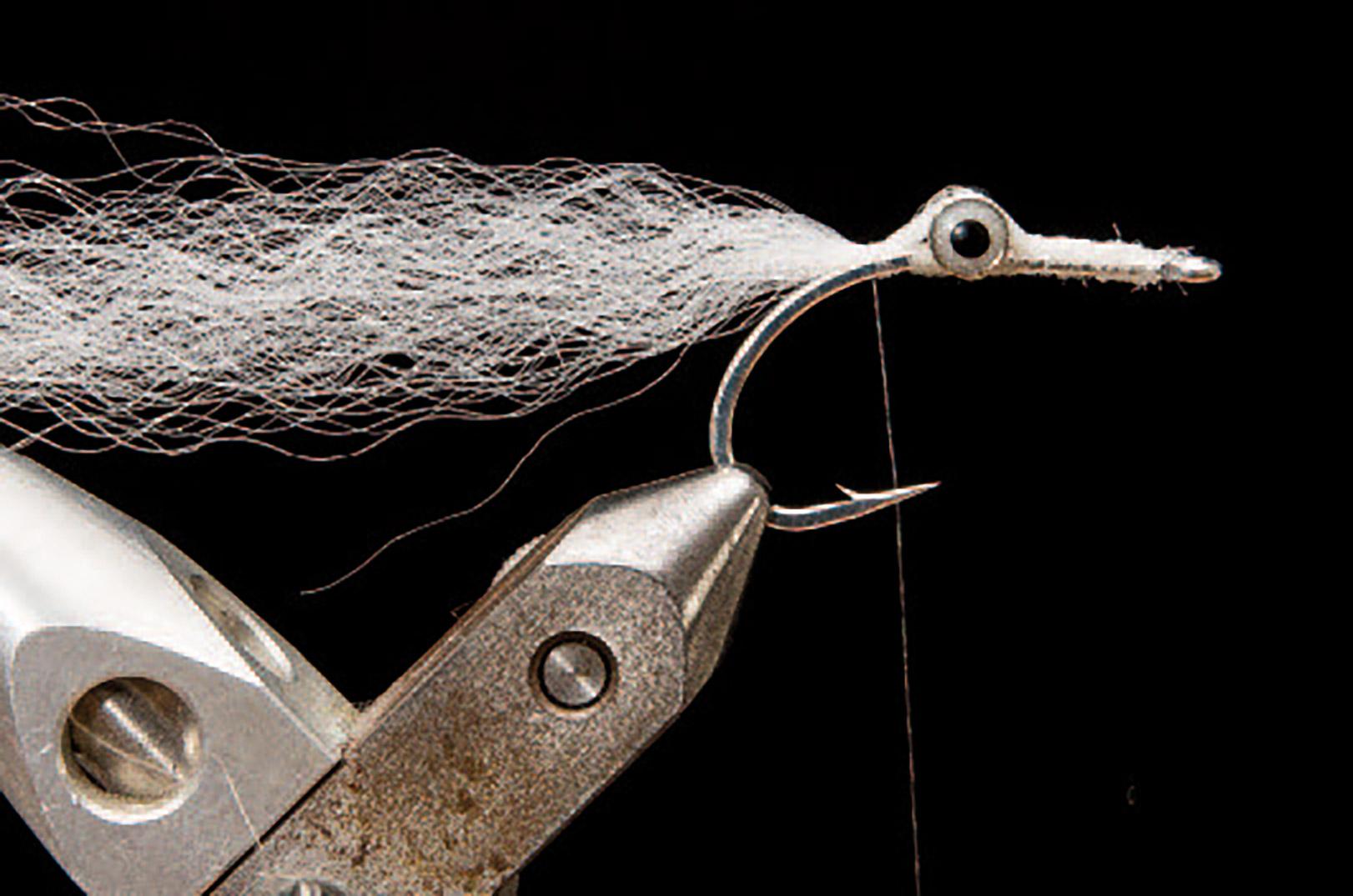 3: Få bindetråden om bag øjnene og bind vingen fast på oversiden af krogen med et par tørn bindetråd.