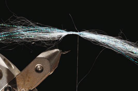 2. Bland et bundt Ghost Hair i farven Light Violet med Krystal Flash i farven pearl. Bind bundtet ind på midten, så der er lige meget materiale på begge sider af bindetråden. Tørn bindetråden hele vejen frem til krogøjet.
