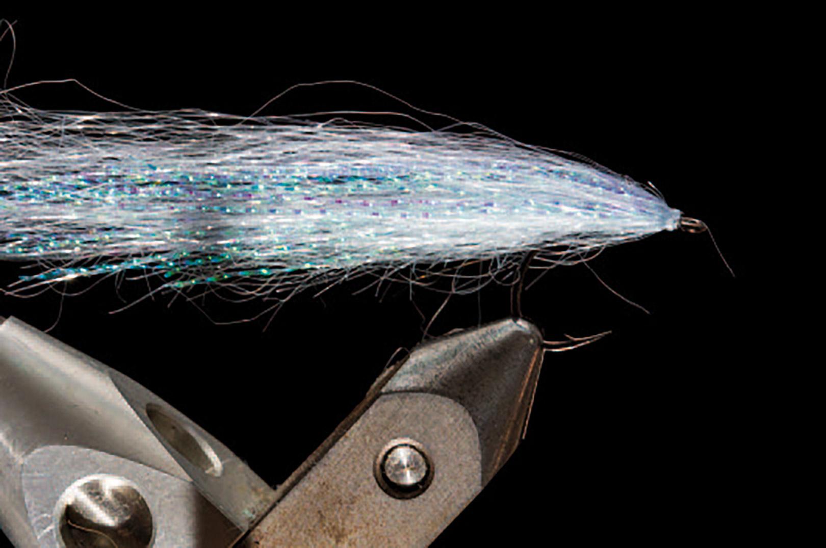 5. Bind et lille bundt light Violet Ghost Hair og fordel det rundt om hele fluen. Afslut med et par knuder. Det sidste lag Ghost Hair er vigtigt, da det holder den lidt umedgørlige Krystal Flash på plads »inde i vingen«.