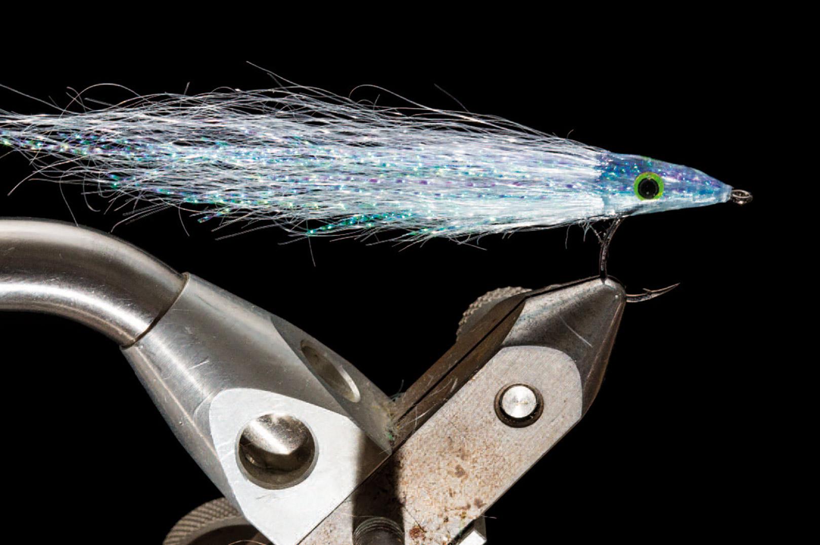 6. Monter et par øjne og dæk hovedet i UV-lim eller epoxy. Forsøg at få en høj og smal profil på fluen – og gå gerne en bid bag krogbøjningen med limen. Det medvirker langt færre ophægtninger af vingen og derved en mere effektiv fisketid. Klip fluen til i den ønskede form og amputer de flashstrå, som ikke vil rette ind med resten af vingen.