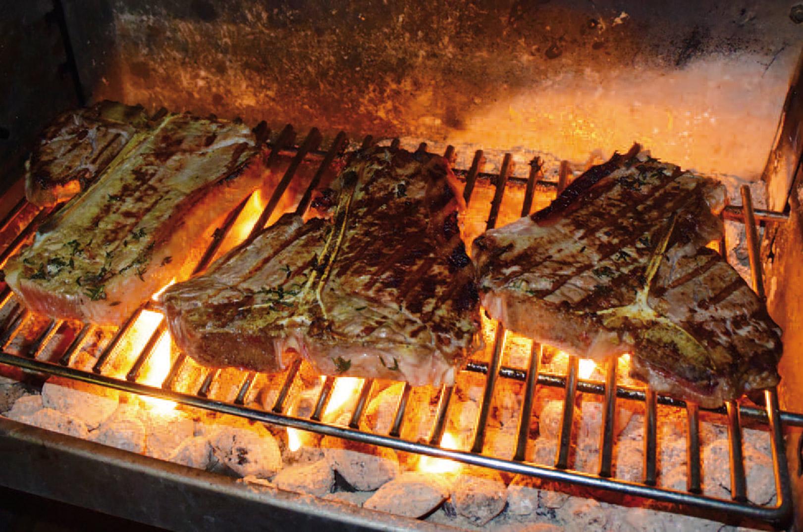 Et par gode bøffer fra det lokale slagteri ryger på grillen om aftenen i sommerhuset.